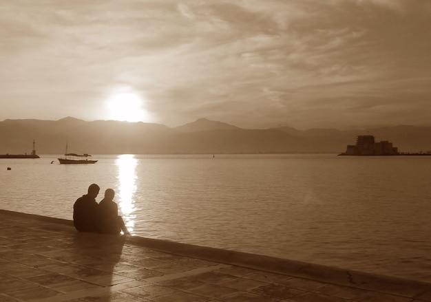 Silhouette d'un couple sur la promenade du bord de mer au coucher du soleil en ton sépia