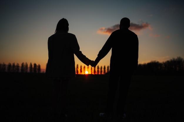 Silhouette de couple romantique main dans la main