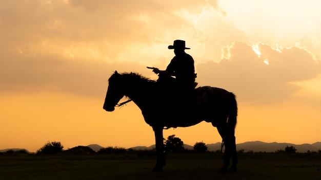 Silhouette de cow-boy à cheval contre un beau coucher de soleil