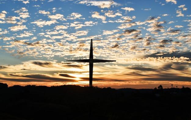 Silhouette de croix chrétienne et éoliennes au coucher du soleil
