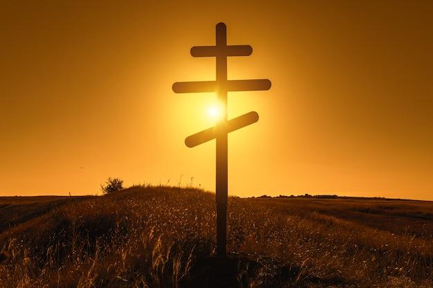 Silhouette de croix orthodoxe chrétienne au coucher du soleil.