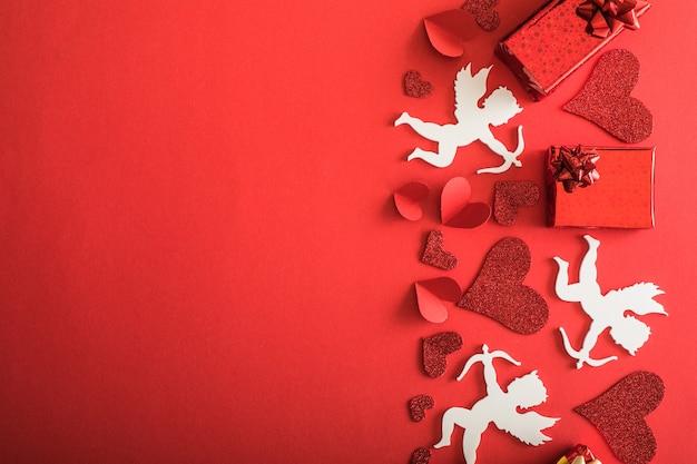 Silhouette de cupidon volant avec des coeurs, des cadeaux, des bannières de la saint-valentin heureuse, style art papier. amour sur papier rouge