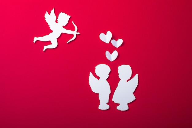Silhouette de cupidon volant, deux anges blancs, bannières de la saint-valentin heureuse, style art papier. amour sur papier rouge