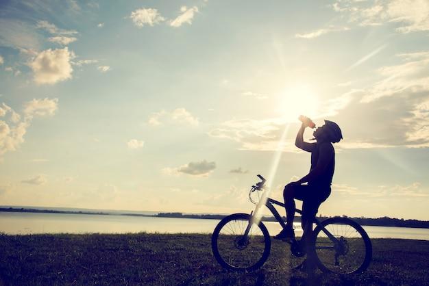 Silhouette de cycliste au repos et à l'eau potable cycliste au coucher du soleil.
