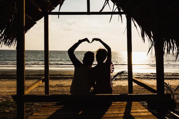 Silhouette deux amants assis sur la cabane
