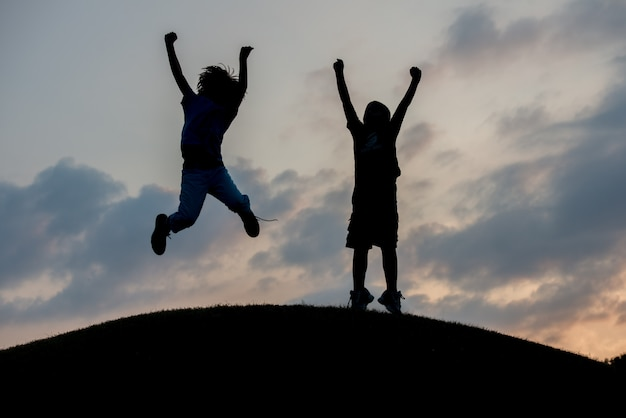 Silhouette de deux frères appréciant la liberté