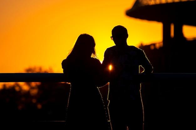 Silhouette de deux personnes amoureuses sur fond de soleil couchant. romance dans les relations et la nature