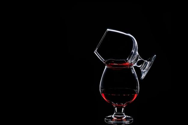 Silhouette de deux verres avec du vin rouge isolé sur fond noir
