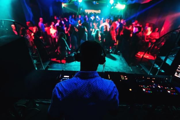 Silhouette de dj jouant de la musique sur table de mixage et beaucoup de gens dansant en discothèque sur scène