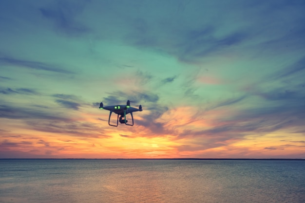 Silhouette de drone quad hélicoptère volant dans le ciel