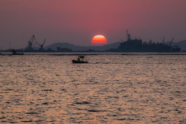 La silhouette du bateau de pêche au coucher du soleil