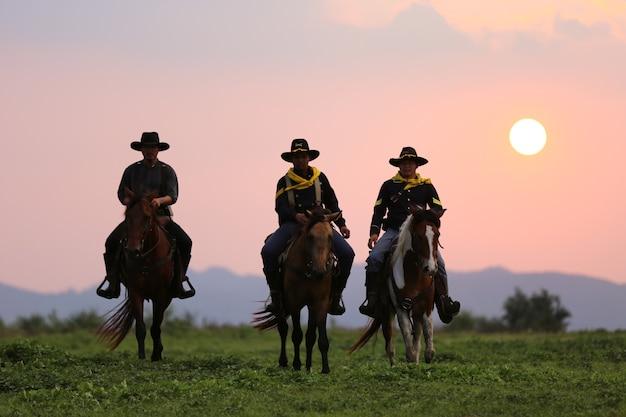 La silhouette du cavalier en costume de cow-boy avec des chevaux et un pistolet tenu à la main sur fond de fumée et de coucher de soleil