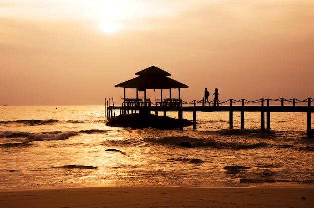 Silhouette du couple marchant sur le pavillon avec ciel coucher de soleil