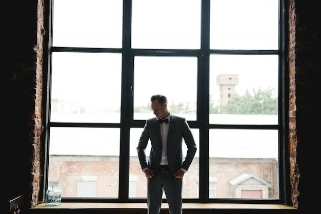 Silhouette du gars devant la fenêtre. matin du marié. chambre de style loft. grandes fenêtres.