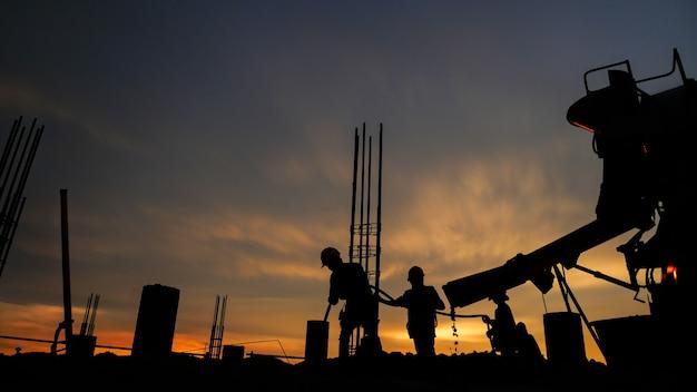 Silhouette du groupe de travailleurs travaillant sur un chantier de construction.