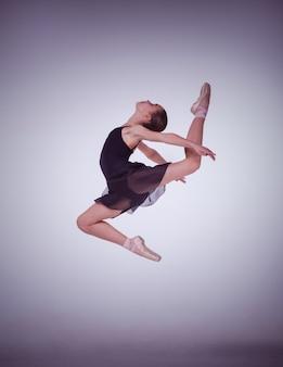 La silhouette du jeune danseur de ballet sautant sur un fond lilas.