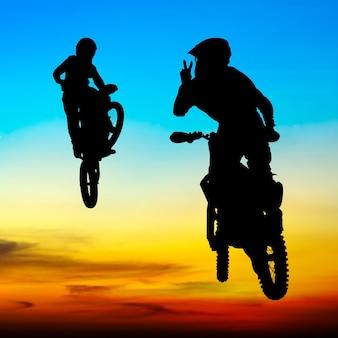 Silhouette du motocross cavalier sauter dans le ciel au coucher du soleil