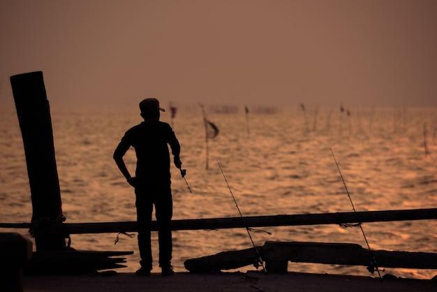 La silhouette du pêcheur avec ciel coucher de soleil
