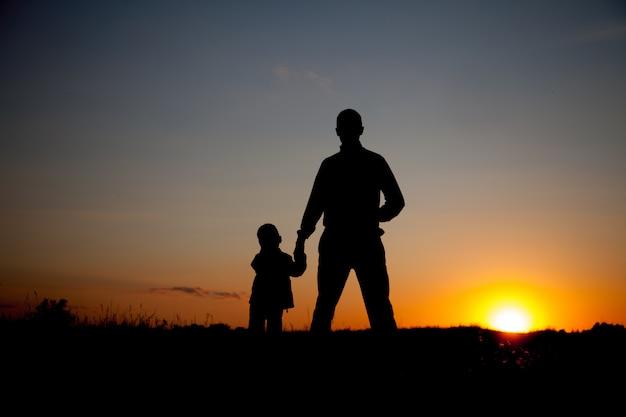 Silhouette du père et du fils, tenant par la main au coucher du soleil