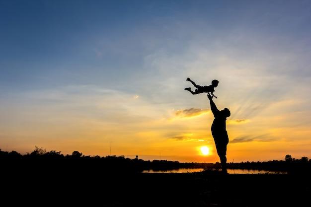 Silhouette du père qui jette son fils dans le ciel. père et fils au fond du coucher du soleil
