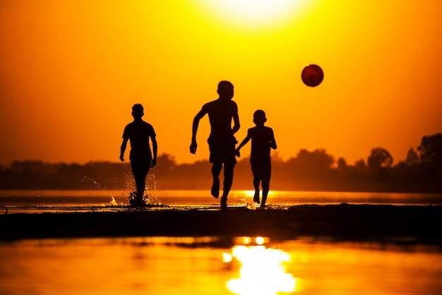 Silhouette d'enfants jouant au football sur la plage