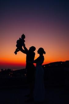 Silhouette d'une famille avec enfants dans le contexte du soleil couchant et de la mer au monténégro.