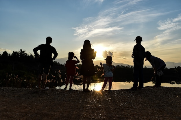 Silhouette d'une famille heureuse au barrage au coucher du soleil avec un ciel bleu.