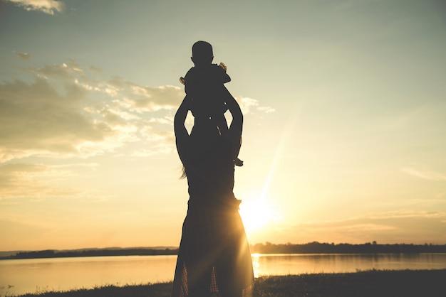Une silhouette d'une famille heureuse jeune mère harmonieuse à l'extérieur.