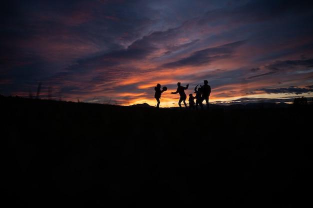 Silhouette d'une famille jouant avec une balle à l'extérieur sur une colline au coucher du soleil