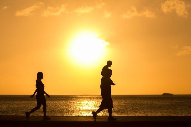 Silhouette de famille marchant sur la plage avec bébé sur le cou