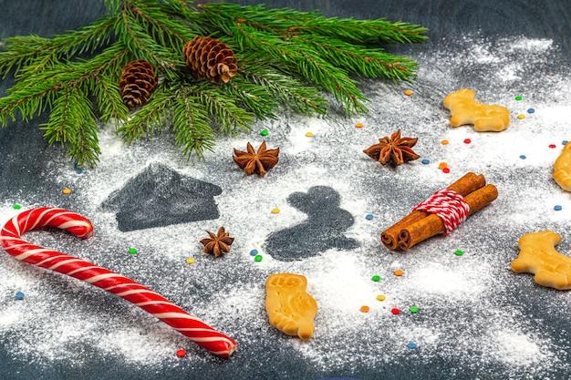 Silhouette de farine de cookies sur fond sombre parmi les branches d'arbres de noël, les cônes, l'anis étoilé, la cannelle et la canne en bonbon.