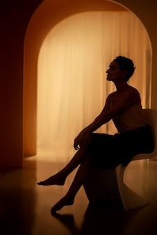 Silhouette féminine assise sur une chaise dans l'arcade éclairée par une douce lumière chaude
