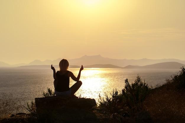 Silhouette femme adulte pratiquant le yoga près de la mer au coucher du soleil.
