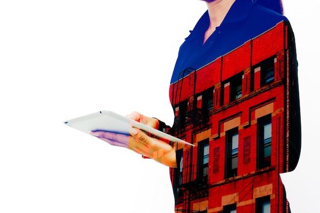 Silhouette d'une femme d'affaires travaillant par tablette avec immeuble d'appartements et fond blanc. double exposition.