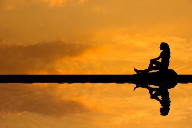 Silhouette d'une femme asiatique assise et à la recherche de quelque chose