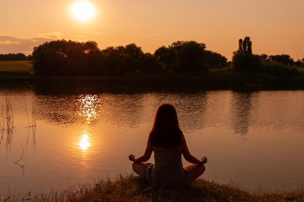 Silhouette d'une femme assise en tailleur en méditation sur une colline surplombant le paysage rural