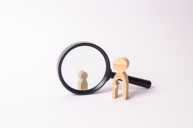 Une silhouette de femme en bois se tient près de la loupe, derrière laquelle se trouve un enfant.