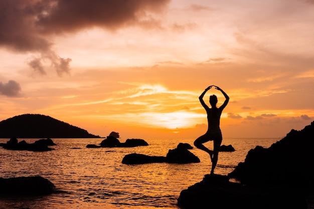 Silhouette de femme contre le coucher du soleil d'été sur la mer