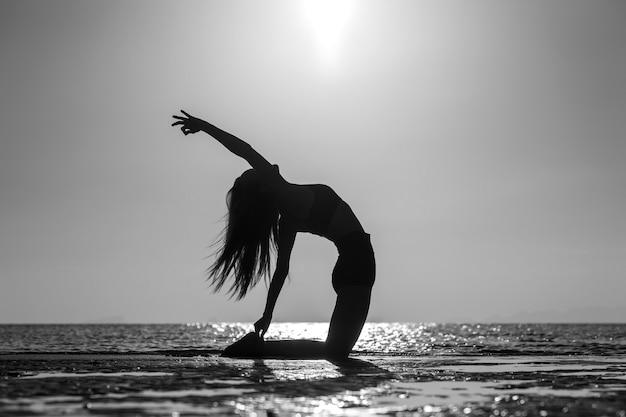 Silhouette de femme debout à la pose de yoga sur la plage tropicale pendant le coucher du soleil. fille caucasienne pratiquant le yoga près de l'eau de mer. noir et blanc