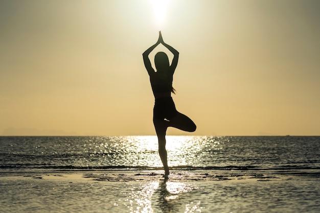 Silhouette de femme debout à la pose de yoga sur la plage tropicale pendant le coucher du soleil. fille caucasienne pratiquant le yoga près de l'eau de mer