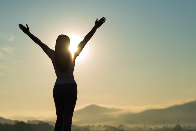 Silhouette de femme écartant les bras et regardant la montagne.