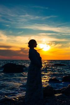 Silhouette d'une femme enceinte au coucher du soleil au bord de la mer