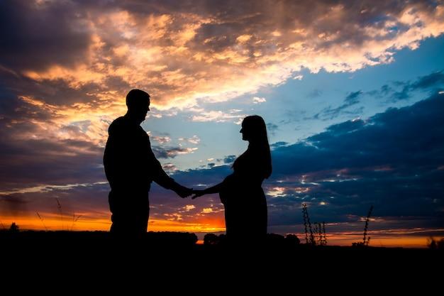 Silhouette d'une femme enceinte et homme debout sur un coucher de soleil face à face, tenant par la main.