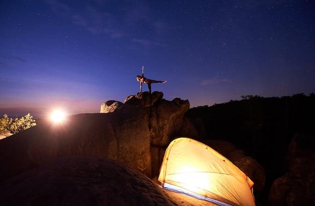 Silhouette de femme faisant des exercices de yoga compliqués au sommet d'un énorme rocher contre le ciel étoilé bleu dramatique dans la soirée