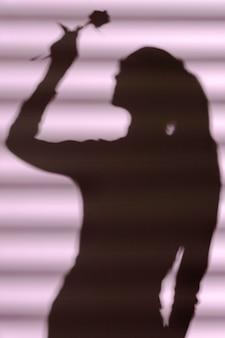 Silhouette de femme à la maison avec des ombres de fenêtre