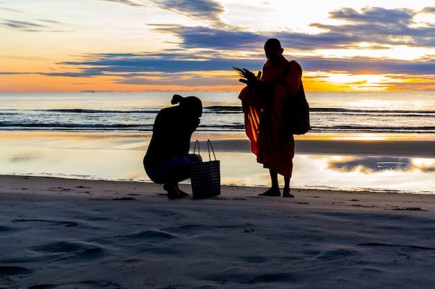 Silhouette de femme ob la plage du coucher du soleil faisant le mérite avec de la nourriture en thaïlande.
