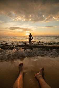 Silhouette de femme sur la plage au coucher du soleil avec les jambes de l'homme