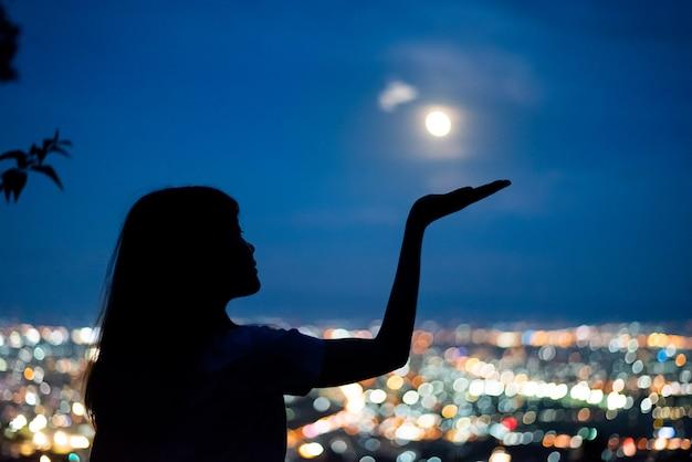 Silhouette, femme, portrait, à, pleine lune, dans, ville, lumière nuit, bokeh, fond, chiang mai, thaïlande