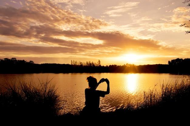 Silhouette de femme prenant une photo au bord du lac