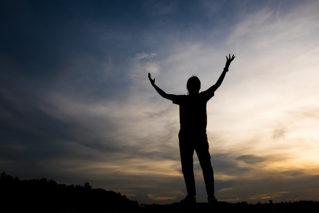 Silhouette de femme priant avec dieu